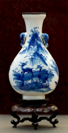 Chinese antique blue and white vase, Museum quality on wooden stand with brown background  Stock Photo