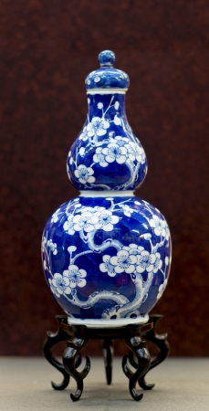 Chinese antique blue and white vase, Museum quality on wooden stand with brown background  Archivio Fotografico