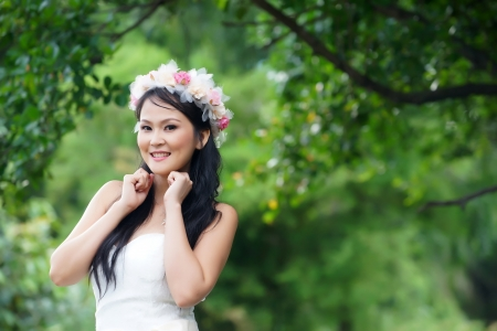 Beautiful Asian lady in white bride dress, posing in the forest, greenery in the background, model is Thai Ethnicity. Stock Photo