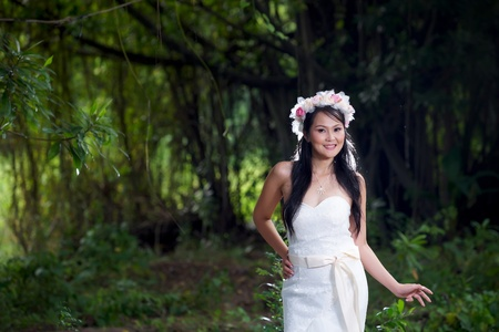 thai ethnicity: Beautiful Asian lady in white bride dress, posing in the forest, greenery in the background, model is Thai Ethnicity. Stock Photo