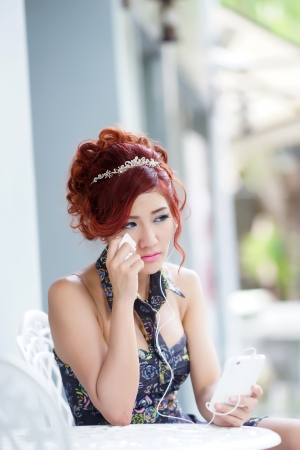 Beautiful woman upset and crying,  She using smartphone listen melancholic music or get unhappy phone call while sitting at outdoor cafe, model is Thai Ethnicity. photo
