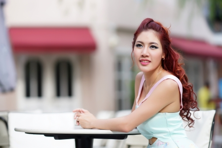 thai ethnicity: Beautiful young woman sitting alone in street cafe, Model is Thai Ethnicity.