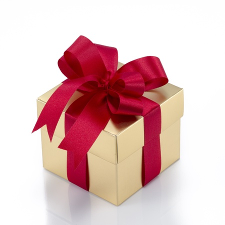 Beautiful gold present box with red bow and ribbons on white backgound