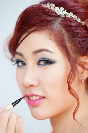 thai ethnicity: Beauty woman applying lipstick on lips with brush, Model is Thai Ethnicity.