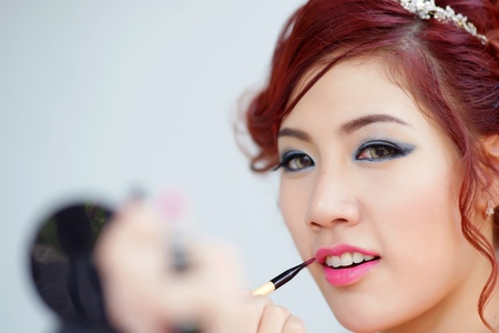 Beauty woman applying lipstick on lips with brush, Model is Thai Ethnicity. photo