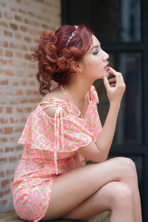 thai ethnicity: Young pretty woman sitting on wooden bench, against brick wall background. Model is Thai Ethnicity.