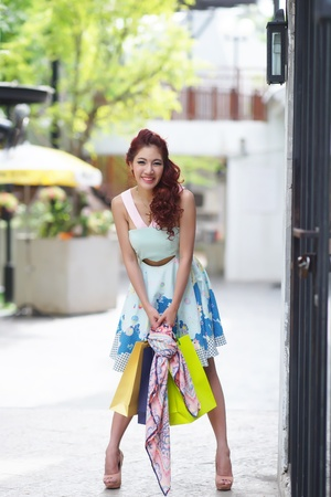 Young beautiful woman shows an ecstatic expression while holding shopping bags outside shopping mall. photo