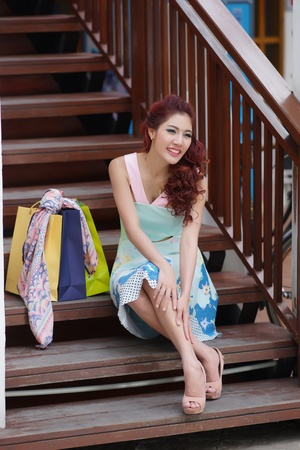 thai ethnicity: Happy woman taking a break with shopping bags while sitting on the stairs, Model is Thai Ethnicity.