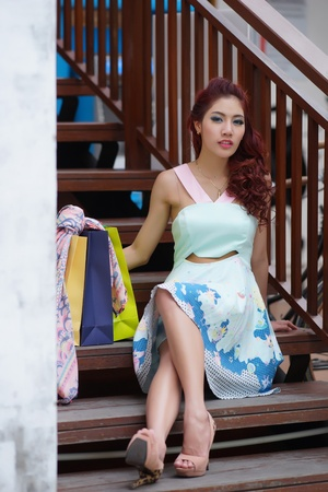 Happy woman taking a break with shopping bags while sitting on the stairs, Model is Thai Ethnicity.  photo
