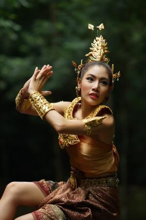 Piękna pani w Thai Thai tradycyjny strój dramatu, stwarzających w lesie, zieleń w tle, model jest Thai Rasa.
