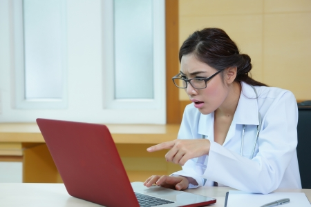 Young female doctor pointing to laptop screen with surprised, Model is Asian woman.  Banco de Imagens