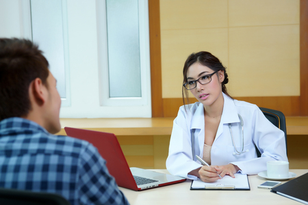 Woman doctor talking to her male patient at office, Mode is Thai ethnic. photo
