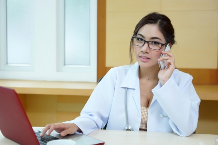 Young doctor woman speaking by phone mobile in her office. photo