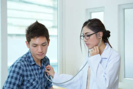 Young woman doctor auscultating male with stethoscope in office room photo