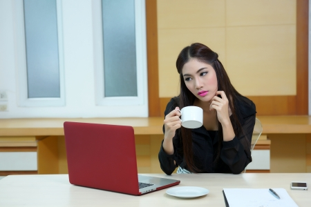 Business woman hold cup of coffee sitting at the desk with laptop photo