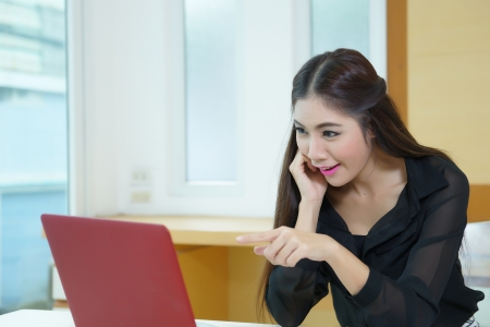 Young business woman surprised pointing to laptop screen. photo