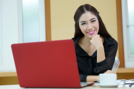 Young pretty business woman with notebook in the office. photo