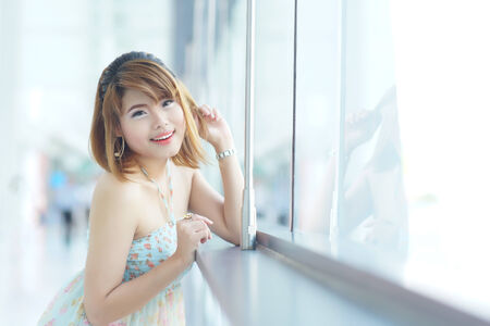 beautifull woman: Young beautifull woman stand near glass wall in office. Stock Photo