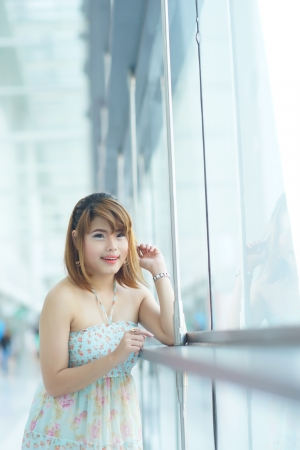 Young beautifull woman stand near glass wall in office. photo