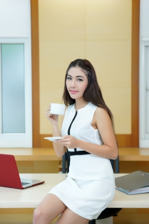 Beautiful Asian business woman holding coffee cup at her desk in office.
