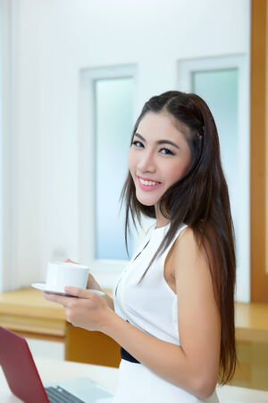 Beautiful Asian business woman holding coffee cup at her desk in office. photo