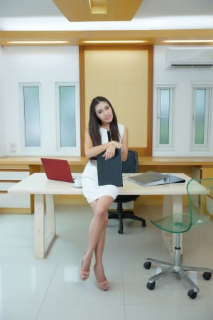 Beautiful Asian business woman standing at her desk in office.