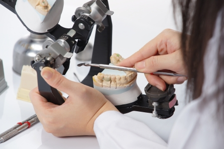 lab technician: Dental technician working with articulator in dental laboratory