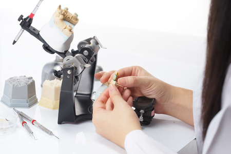 prosthetic equipment: Dental technician working with articulator in dental laboratory