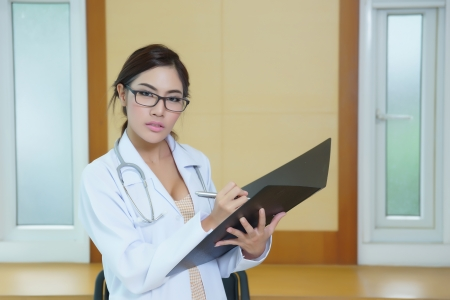 Young beautiful doctor writing on folder photo