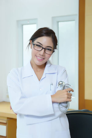 Portrait of happy successful young female doctor holding a stethoscope  photo