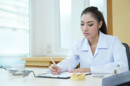 Attractive young female doctor sitting at desk in office doing paperwork.  photo