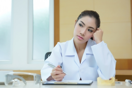 Bored woman dentist looking very boring at her desk.
