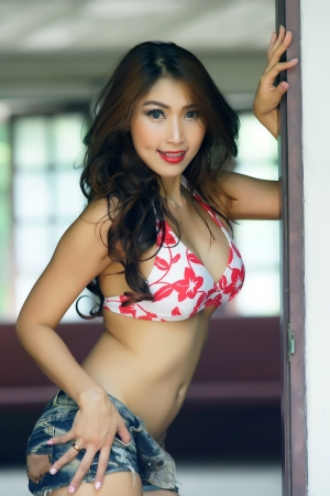 Young beautiful Asian woman in red bikini with short pants jean, voluptuous posing outdoors  photo