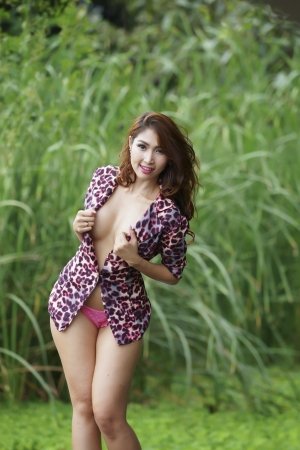Beautiful sexy Asian girl posing topless outdoors photo