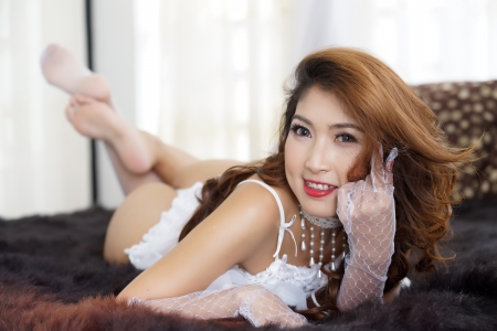 Beautiful Asian woman in sexy lingerie in bedroom photo