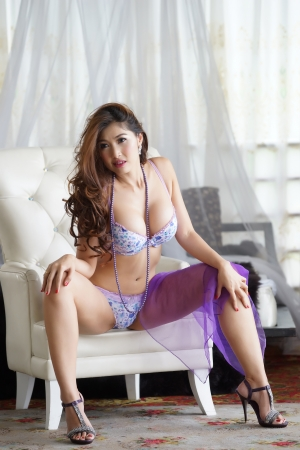 sexy young woman in lingerie sitting in the armchair posing  sitting in the white armchair photo