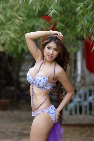 Beautiful Asian woman in lingerie voluptuous posing outdoors.  photo
