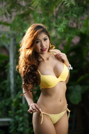Beautiful Asian woman in lingerie voluptuous posing outdoors.  Stock Photo