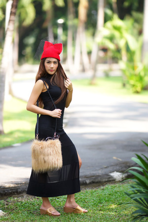 Beautiful Asian lady in black dress, posing in the park, greenery in the background, model is Thai Ethnicity. photo