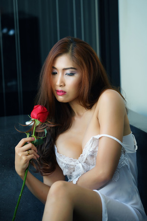 nightdress: Sexy woman in white nightdress and holding red rose Stock Photo