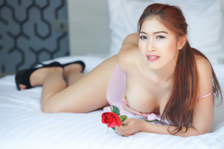 Sexy woman in pink nightdress, holding red rose posing on the bed photo