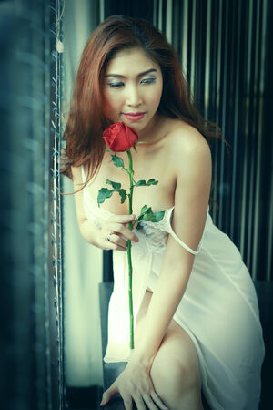 Sexy woman in white nightdress, holding red rose posing near the window photo