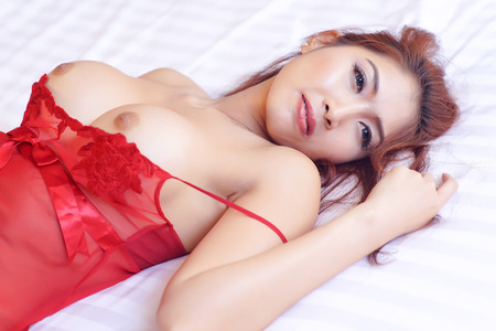 Sexy woman topless lying on bed. Open eyes.