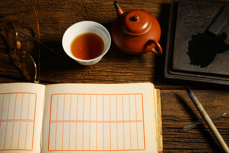Chinese calligraphy and ink stone set on table with tea bowl, teapot, eyeglasses. Warm tone color. photo