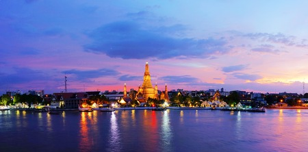 Panorama view of Twilight time Wat Arun across Chao Phraya River during sunset in Bangkok, Thailand