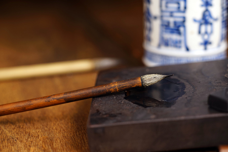 inkstone: Close up of Chinese Writing Brush, focus on the brush. Selective focus with shallow depth of field. Stock Photo