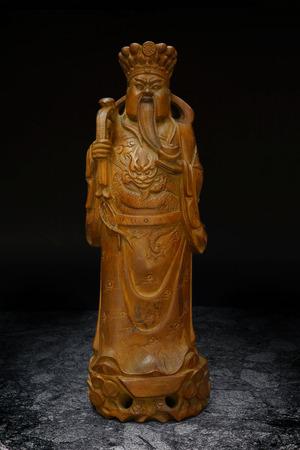 cetro: Tallado en madera Estatua de la Prosperidad Dios Dinero Holding Gold Bar y Ruyi Scepter Foto de archivo