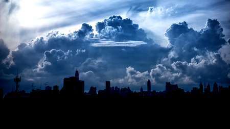 Dark blue storm clouds over city in rainy season. Stock Photo
