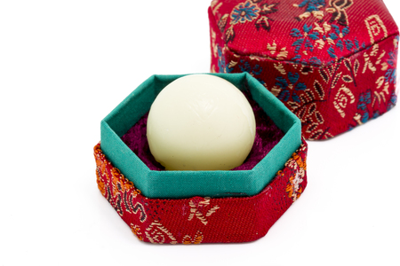 bolus: White wax capsule of Chinese medicine in red hexagon box, isolated on white background.