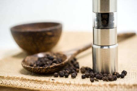 peppercorn: Pepper grinder and black peppercorn. Stock Photo
